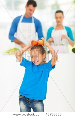 little girl having fun with tomatoes while her parents cooking in kitchen