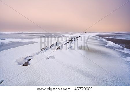 Old Breakwater In North Sea Under Snow
