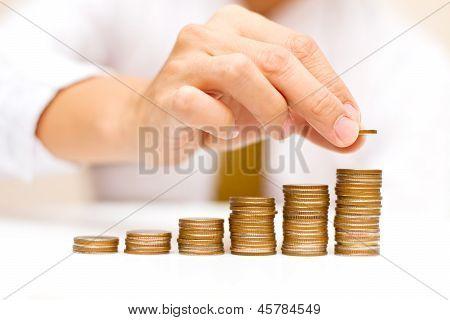 Un hombre subiendo monedas