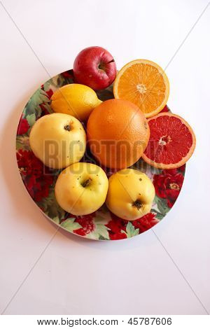 plate with orange grapefruit and apples