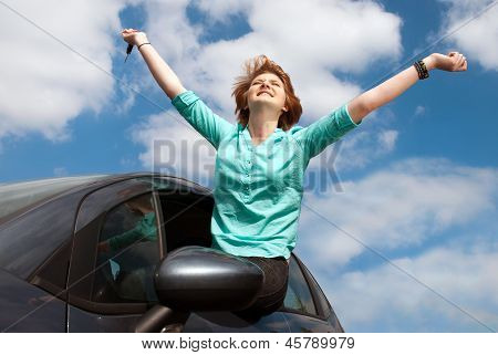 Young Woman Sitting In The Car And Holding A Key Against Blue Sky