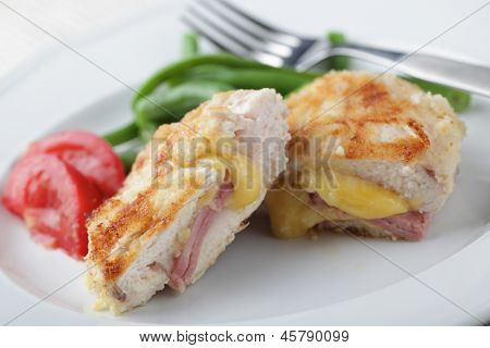 Chicken schnitzel Cordon blue with vegetables on white plate closeup
