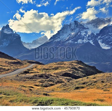 The gravel road is bent between yellowed hills and go to the snow-covered rocky mountains. Midday landscape in the national park Torres del Paine, Chile