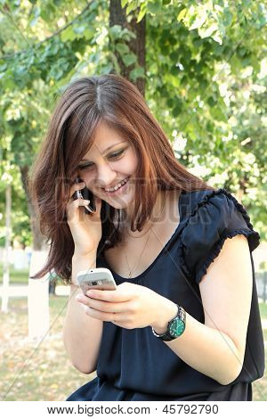 Girl Speaking On Two Mobile Phones