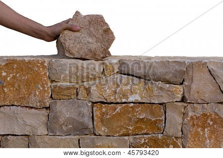 Mason hands working on masonry stone wall stonewall