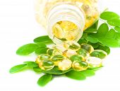 Herbal Medicine Oil Pills With Green Plant On White Background