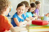 image of diligent  - Portrait of happy diligent pupil looking at her classmate at lesson - JPG