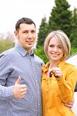 Portrait of happy beautiful couple with car key, standing near the car