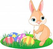 picture of easter bunnies  - A cute Easter bunny standing near brightly colored eggs - JPG