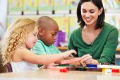 stock photo of pupils  - Elementary Pupils Counting With Teacher In Classroom - JPG