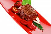 meat savory : beef grilled and garnished with green lettuce and red chili hot pepper on red plate is