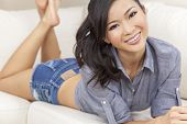 picture of denim wear  - A beautiful young Chinese Asian Oriental woman or girl with a wonderful toothy smile laying down on a sofa wearing denim shorts - JPG