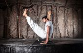pic of ashtanga vinyasa yoga  - Yoga chakorasana pose by Indian man in white cloth in yoga shala Varkala Kerala India - JPG