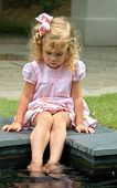 pic of hair bow  - In a world of her own small blond haired child wet her feet in pool. Pink dress and hairbow.