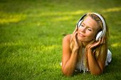 Happiness girl with headphones enjoying nature and music at sunny day.