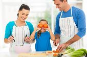 happy young family cooking in kitchen at home