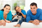 stock photo of daddy  - loving young family lying on bed at home with their pet dog - JPG