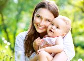 stock photo of young baby  - Beautiful Mother And Baby outdoors - JPG
