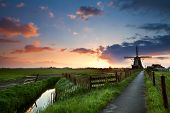 stock photo of pasture  - warm spring sunrise behind windmill - JPG