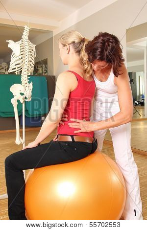 Physiotherapist with patient on gymnastic ball with hands on spine