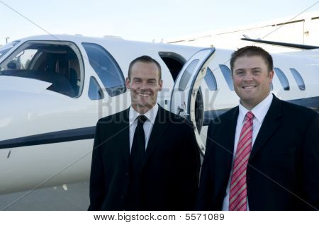 Businessmen Standing In Front Of Corporate Jet