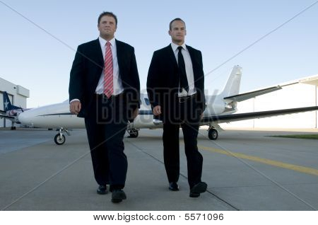 Businessmen Walking Away From Corporate Jet