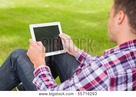 Happy student using his tablet outside on college campus