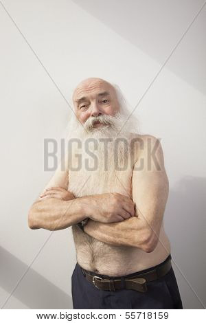 Portrait of shirtless senior man with arms crossed over white background