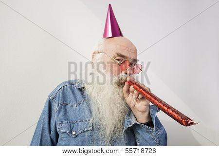 Portrait of senior man wearing party hat while blowing horn against gray background