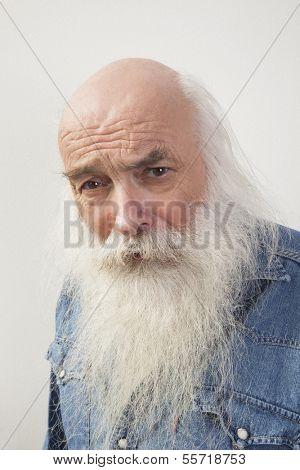 Portrait of suspicious senior man over gray background