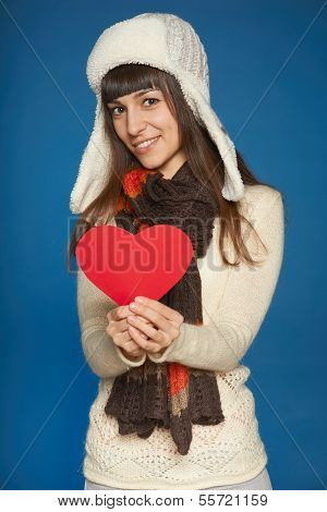 Winter woman in warm clothing giving heart shape