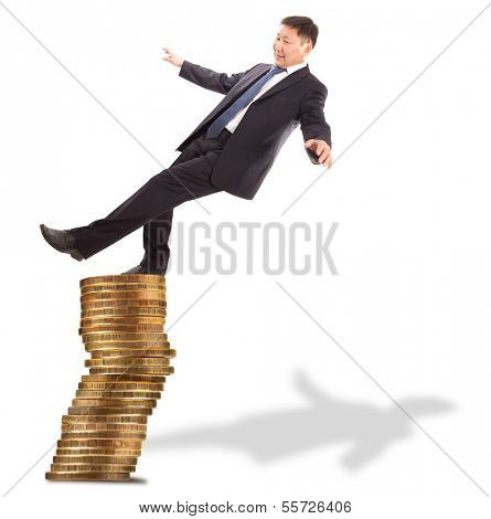 Financial and crisis concept. Asian businessman standing on the unstable coins