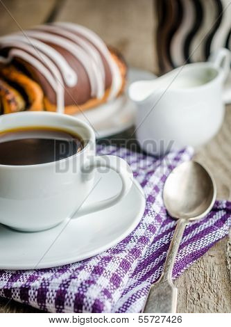 Cup Of Coffee And Poppy Bun Glazed With Ganache