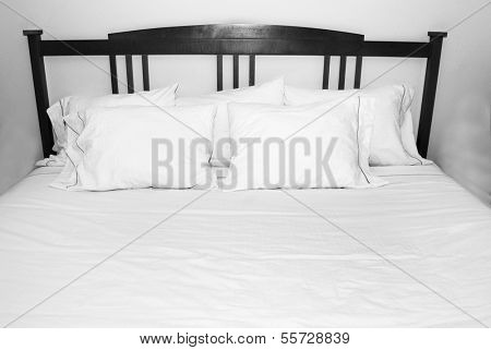 Group of several white pillows on a white bed with wooden headboard