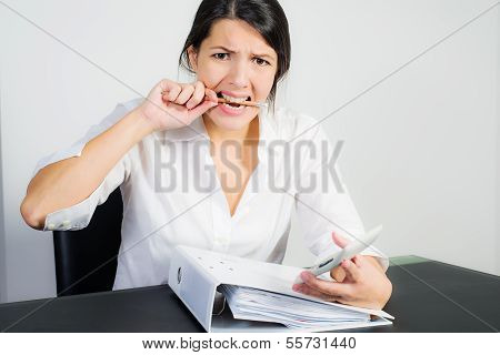Businesswoman Biting Her Pen In Frustration