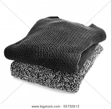 some folded sweaters on a white background