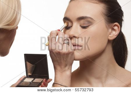 Beautician applying eye makeup to the eyelids of an attractive young model before a photo shoot or stage performance