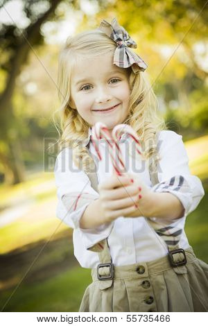 Cute Little Girl with a Bow in Her Hair Holding Her Christmas Candy Canes Outdoors.