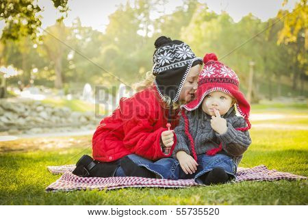 Little Girl Whispers A Secret to Her Baby Brother Wearing Winter Coats and Hats Sitting Outdoors at the Park.