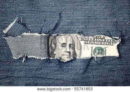 Hundred Dollars Bill Through Torn Blue Jeans Texture