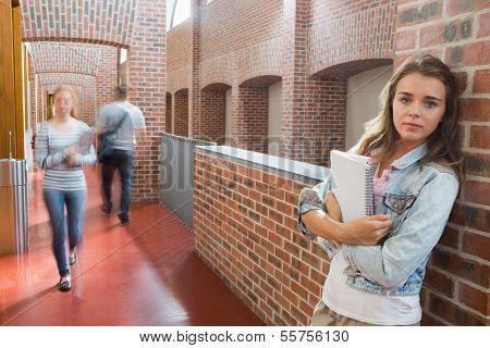 Student leaning against wall in the corridor looking at camera at the university