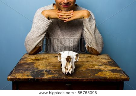 Smirking Man With Skull At Desk
