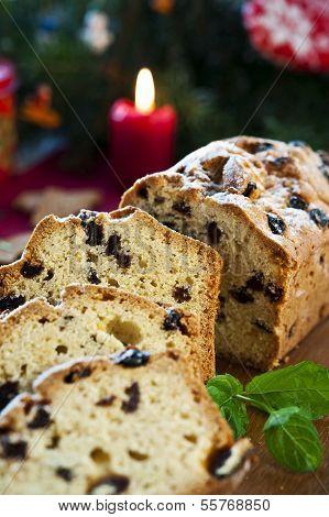 Sliced Fruitcake With Raisins And Mint Leaf On Christmas Background