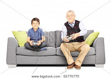 Grandfather with his nephew seated on a sofa playing video games isolated on white background