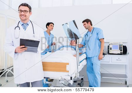 Doctors holding reports by patient in bed at the hospital