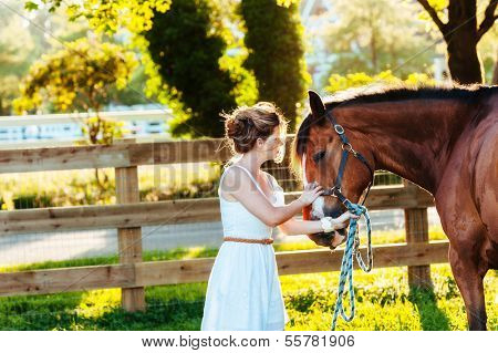a beautiful girl in a white dress and her horse