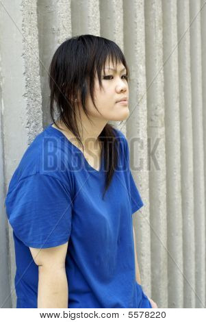Serious looking teen lady leaning on wall