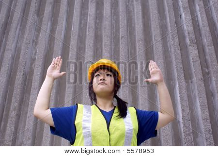 Asian female construction worker with hand signal for stop