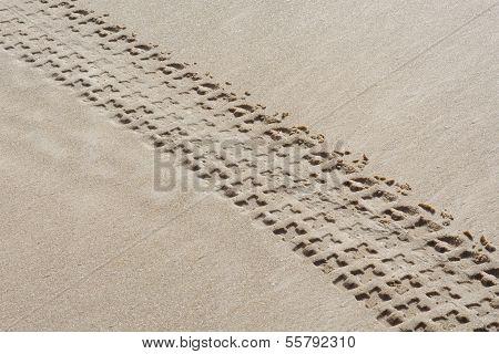 Diagonal track of quad bike on sand
