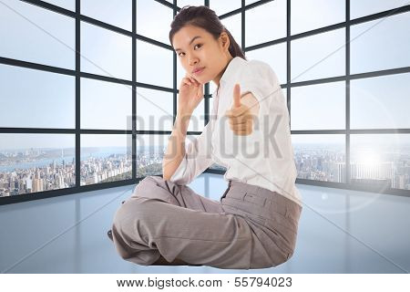 Businesswoman sitting cross legged showing thumb up against room with large windows showing city